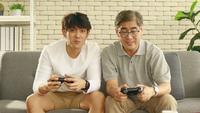 Far och son som har kul med videospel