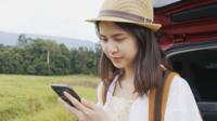 Frau mit Smartphone von einem Auto