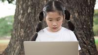 Asian child girl using laptop.