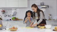 Mor och dotter bakar lyckligt efterrätter i köket.