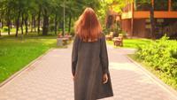 Rothaarige Frau, die in Zeitlupe den Weg entlang geht