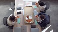 Mitarbeiter essen bei der Arbeit zu Mittag