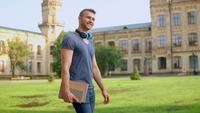 Estudiante guapo camina en un día soleado