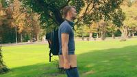 En kille som bär avslappnade kläder går i en stadspark