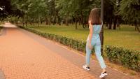 Vista traseira de uma mulher caminhando em um parque da cidade