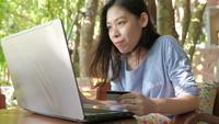 Asian woman holding credit card making online payment.