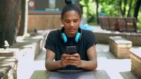 Retrato de un chico de moda sentado en un parque y enviando mensajes de texto