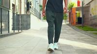 Close-up van de benen van een hipster-kerel die in de stad loopt