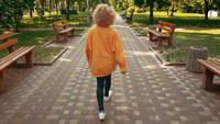 Blonde Frau geht in Stadtpark