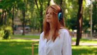 Frau, die Kopfhörer benutzt und Musik draußen hört