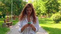 Mulher jovem segurando um celular caminhando na rua