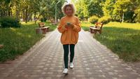 Young woman walking in the park using mobile
