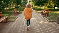 Woman with blond hair using mobile walks outdoors