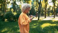 Side view blonde woman scrolls news feed outdoors