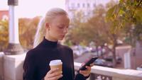 Stående blondin använder telefonen i staden