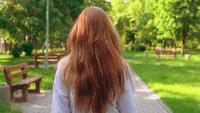 Mujer con cabello largo hermoso se vuelve cara a la cámara
