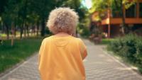 Vista posterior mujer rubia camina en el parque