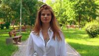 Caucasian female in casual white shirt outdoors