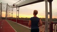 Nicht erkennbare Joggerin läuft auf der Brücke