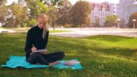Blonde writing in notebook outdoors