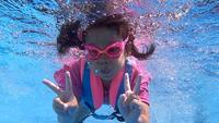 Happy child girl diving underwater in swimming pool.