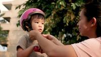 Joven madre ayudando a su hija con casco rosa.