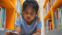Ein kleines Mädchen, das unter vielen Büchern in der Bibliothek liest