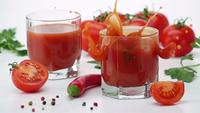 Ripe Tomato Falls into a Glass of Tomato Juice