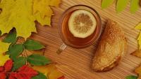 Herbsttee mit Zitronenscheibe und Croissant