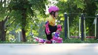 Kleines Mädchen, das Rollschuhlaufen im Park lernt