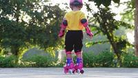 Liten flicka som lär sig rullskridskoåkning i en sommarpark