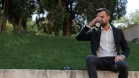 Homem em um parque tomando café