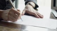 Primer plano de manos de mujer o testigo firmando contrato.