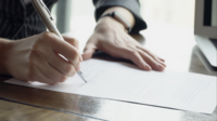 Close-up handen van vrouw of getuige ondertekening contract.